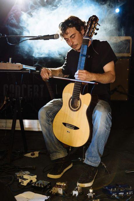 Photo de Paloo du groupe Swallow, jouant de la guitare à l'aide d'un archet